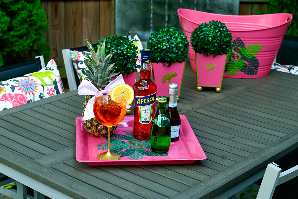 An Aperol Spritz cocktail with an Aperol bottle, sparkling Perrier water and a split of prosecco, pineapple with cute bow, hot pink tray with palm leaves and monogram, how to make an Aperol spritz, aperol spritz ratios, DIY cachepot, cute patio decor