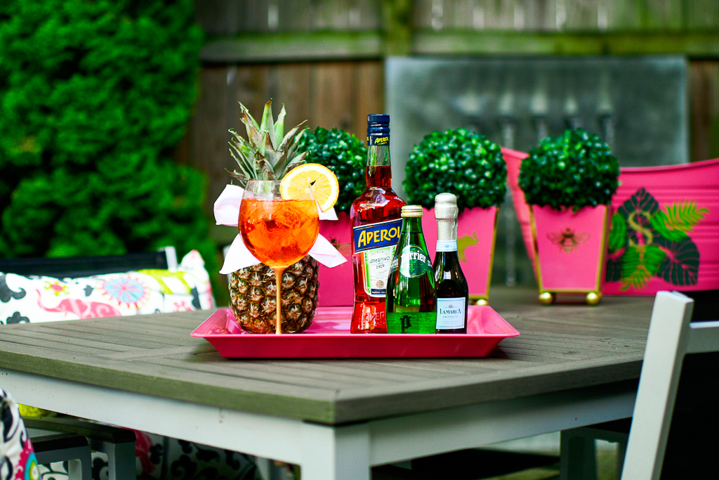 An Aperol Spritz cocktail with an Aperol bottle, sparkling Perrier water and a split of prosecco, pineapple with cute bow, hot pink tray with palm leaves and monogram, how to make an Aperol spritz, pink cachepots, boxwood, patio, aperol spritz ratios.
