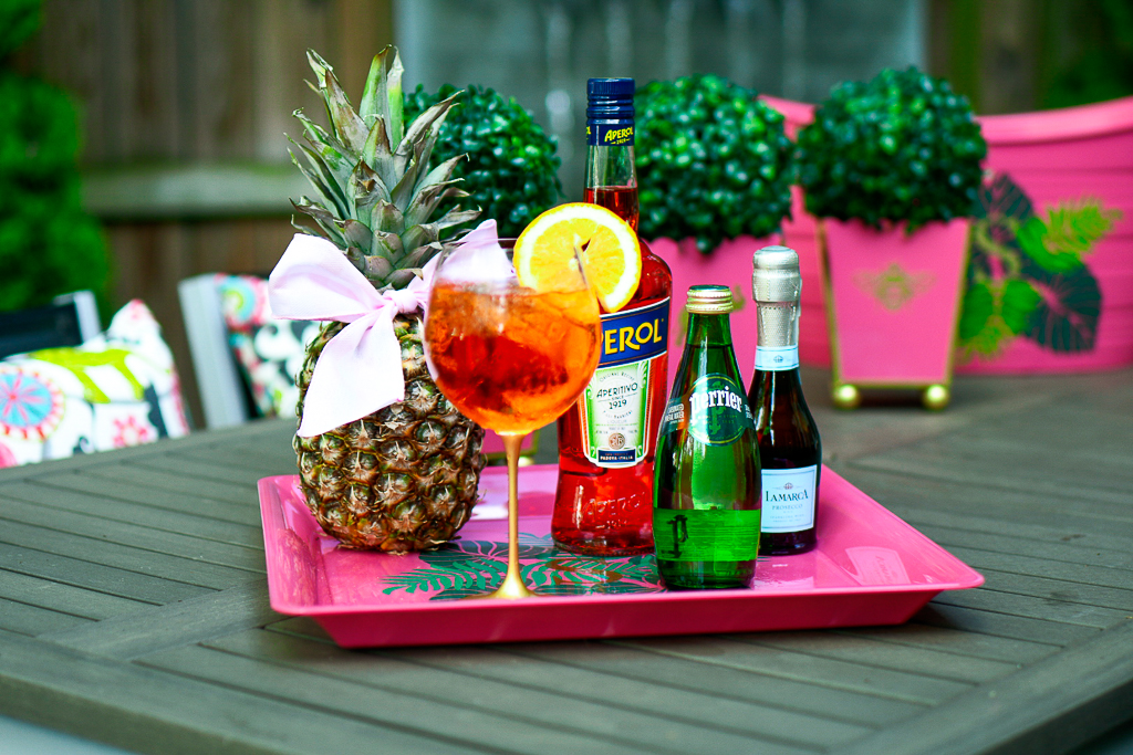 An Aperol Spritz cocktail with an Aperol bottle, sparkling Perrier water and a split of prosecco, pineapple with cute bow, hot pink tray with palm leaves and monogram, how to make an Aperol spritz