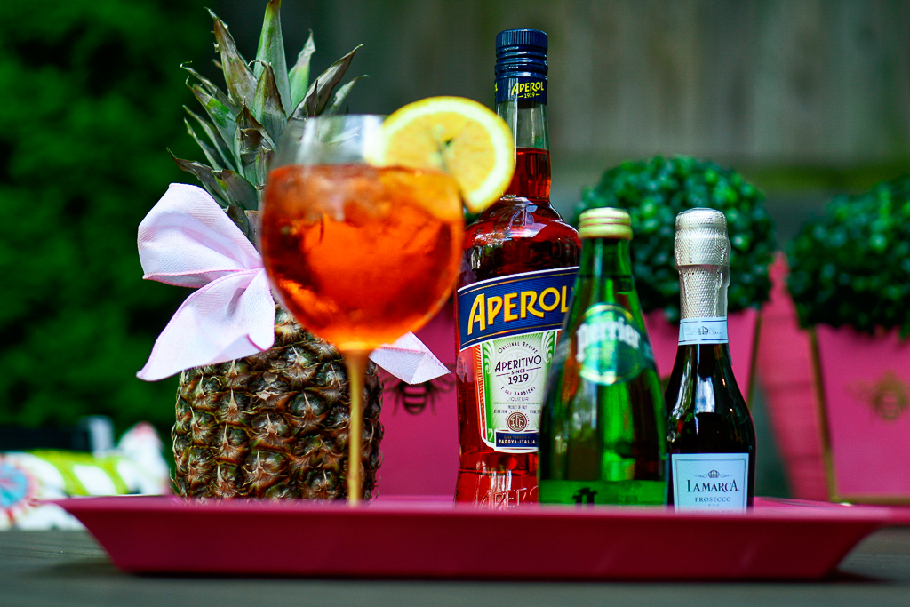 An Aperol Spritz cocktail with an Aperol bottle, sparkling Perrier water and a split of prosecco, pineapple with cute bow, hot pink tray with palm leaves and monogram, how to make an Aperol spritz, Aperol Spritz recipe, Aperol spritz