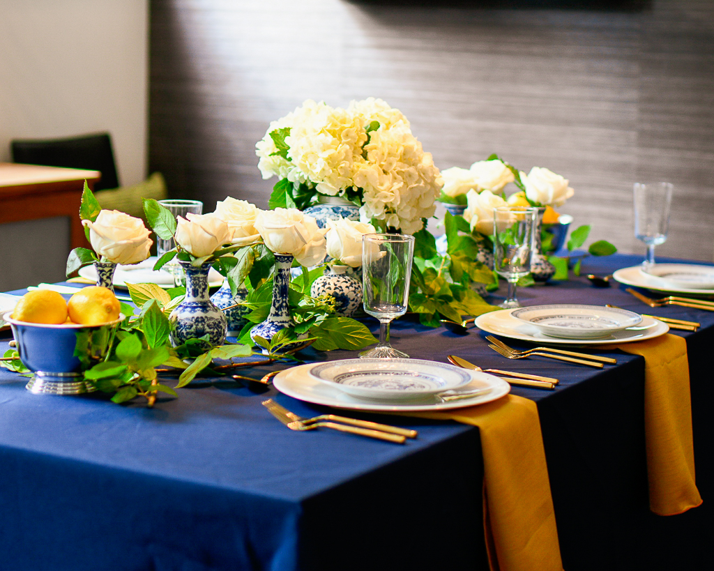 Blue tablecloth with chinoiserie accents, gold flatware and gold napkins, silver bowls with fresh lemons.
