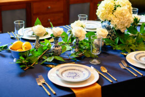 This beautiful blue table setting contains chinoiserie vases with ivory roses, as well as a chinoiserie ginger jar with white hydrangeas. Blue and white china is accented by gold flatware and gold napkins.
