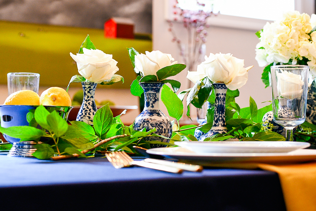 Chinoiserie bud vases with white roses down the center of a table with a navy tablecloth are a great blue table decorations idea.