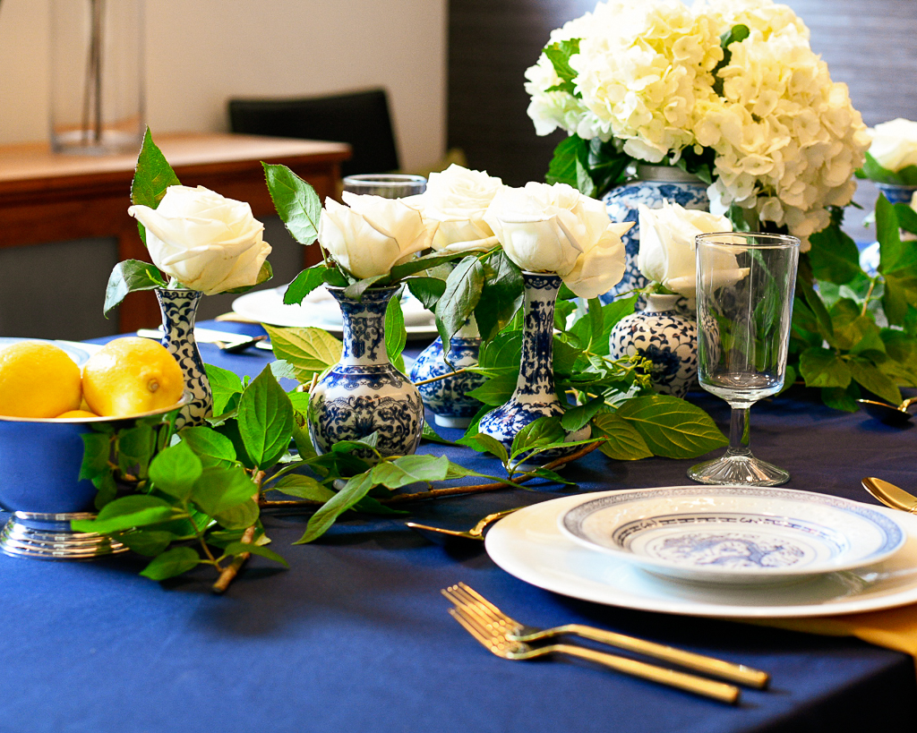 Blue and white tablescape idea with chinoiserie, hydrangeas, white roses, and gold utensils.