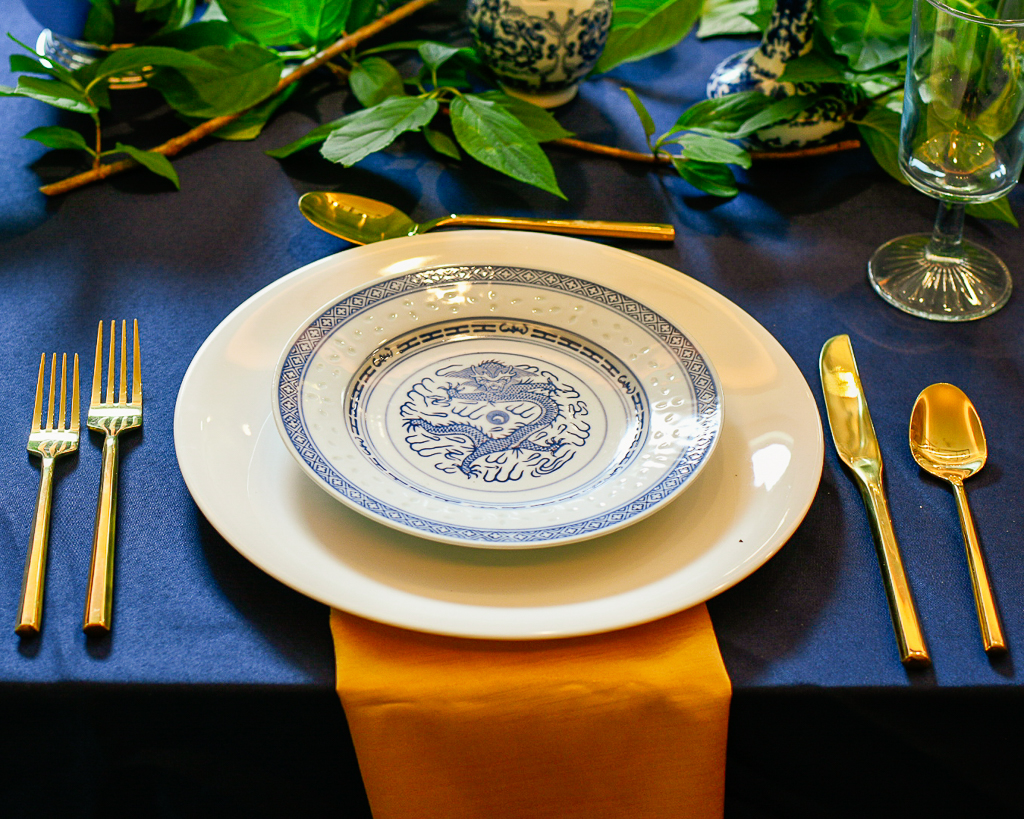 blue and white china, gold utensils, gold napkin, blue tablecloth, chinoiserie vase and white roses combine to illustrate how to use blue table decorations.
