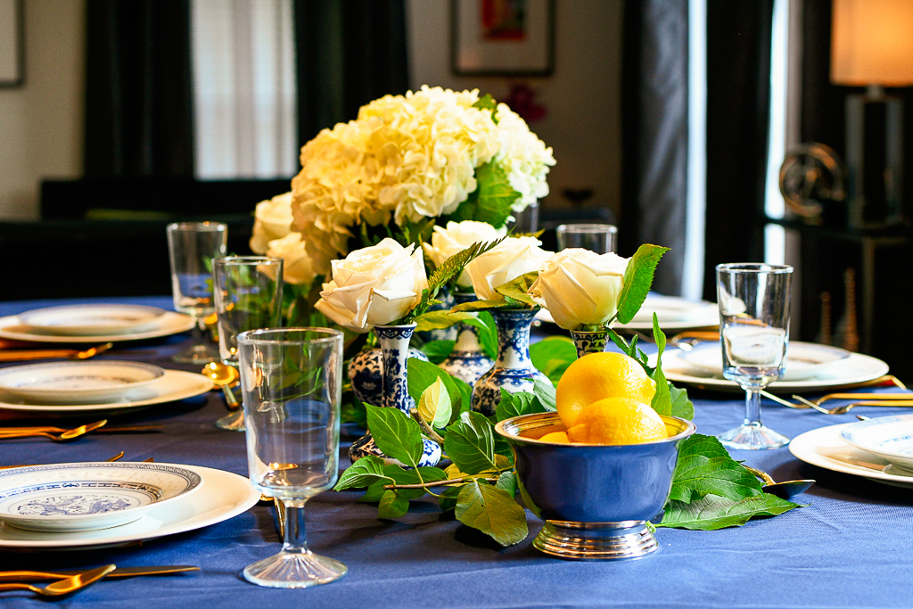 Blue tablecloth, silver bowl with lemons, hydrangeas in a chinoiserie ginger jar.