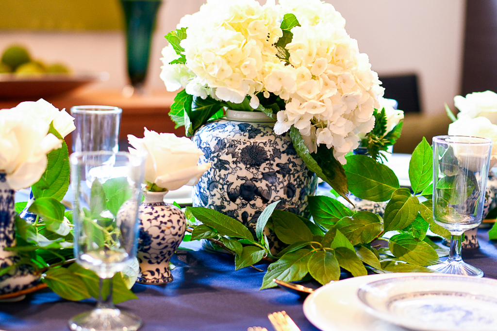 A blue and white chinoiserie ginger jar with white hydrangeas is a perfect centerpiece for the blue table setting.