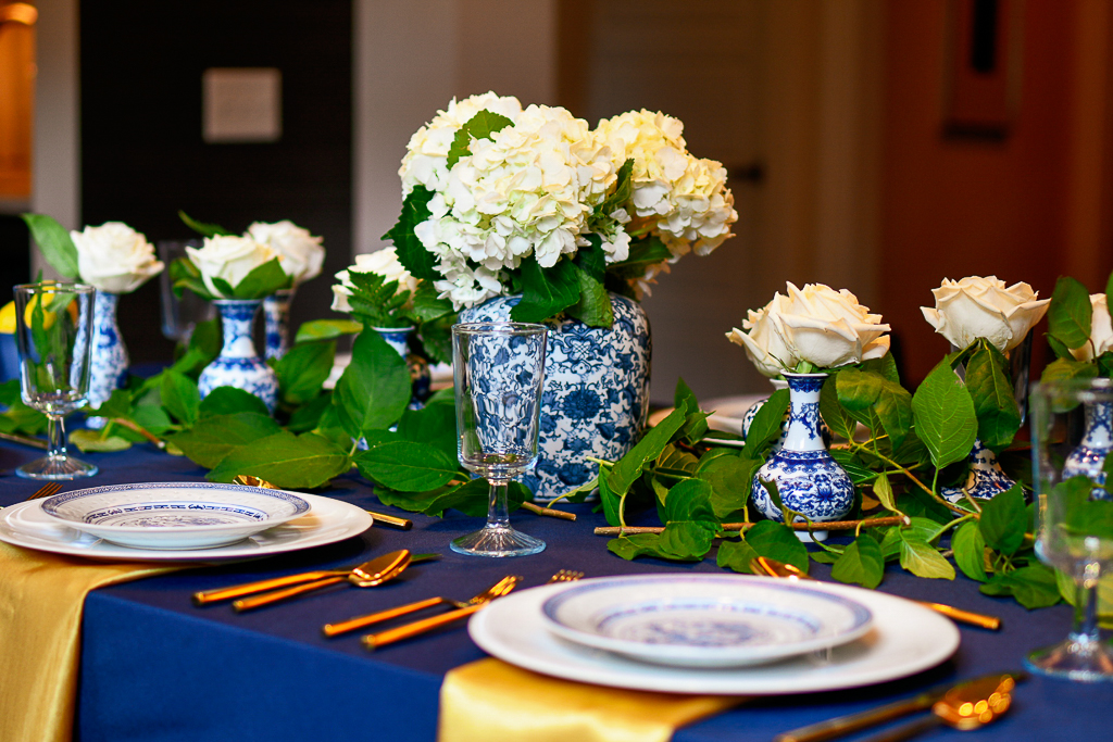 dinner table with navy tablecloth, chinoiserie ginger jar with white hydrangeas, chinoiserie bud vases with white roses, blue table decorations, blue table setting ideas