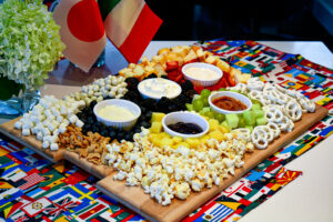 A charcuterie board with fruit arranged as the Olympic rings, assorted nuts, cake and fruit, as well as fruit dips. Olympic party idea.