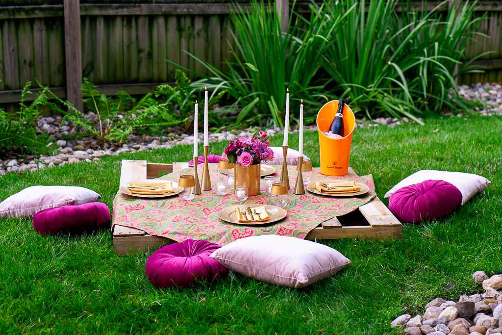 A picnic table that is a wooden pallet, with gold plates, napkins and gold utensils, pale pink velvet pillows, magenta velvet pillows, gold candlesticks, veuve clicquot, and white tapers. Romantic picnic ideas.