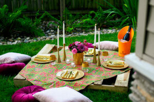 A pallet picnic table sits on green grass with gold chargers, gold flatware, gold candlesticks, white tapers, velvet cushions and a gorgeous bouquet of pink rose, purple daisy, and greenery in a gold vase. Romantic picnic ideas.