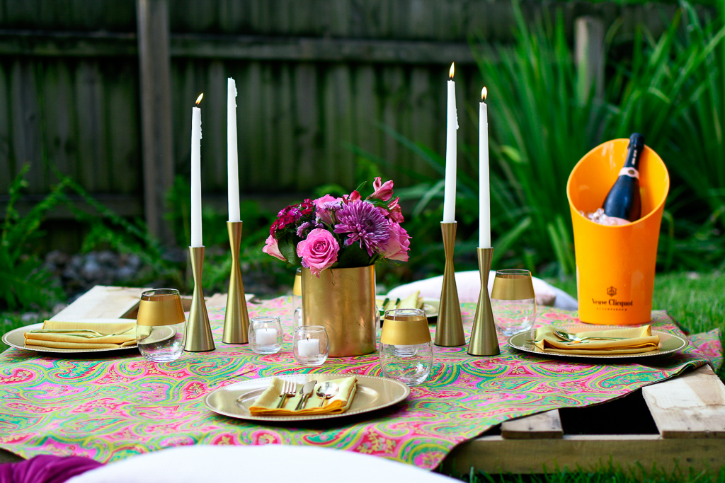 This simple picnic table setting uses a wooden pallet as a table and contains gold candlesticks, gold chargers, gold utensils, gold napkins and a fun paisley table linens. It's an inexpensive and romantic picnic ideas.