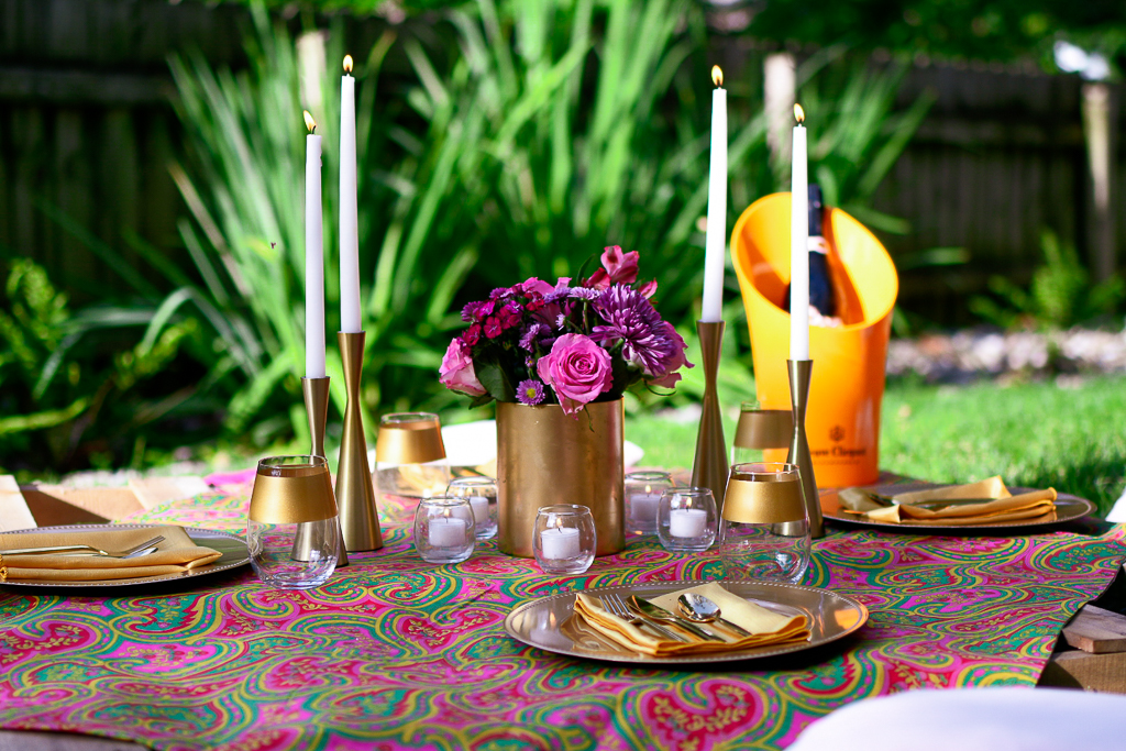 A gorgeous picnic tablescape with gold plates, gold napkins, gold utensils and gold rimmed wine glasses, as well as votive candles, gold candlesticks and white tapers. Easy picnic ideas for couples.