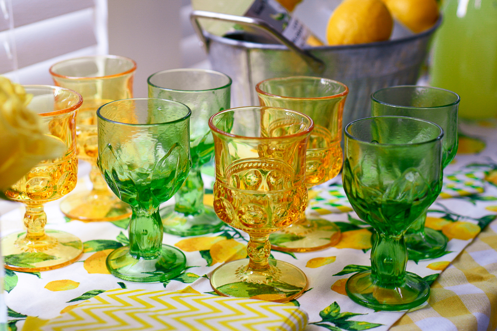 Green vintage glassware, yellow vintage glassware, lemon table runner, yellow and white checked tablecloth, galvanized pail with lemons, all great summer party themes and lemon party theme ideas. It's also cute lemonade stand ideas with lemonade cocktail recipes, as party of a lemonade party idea.