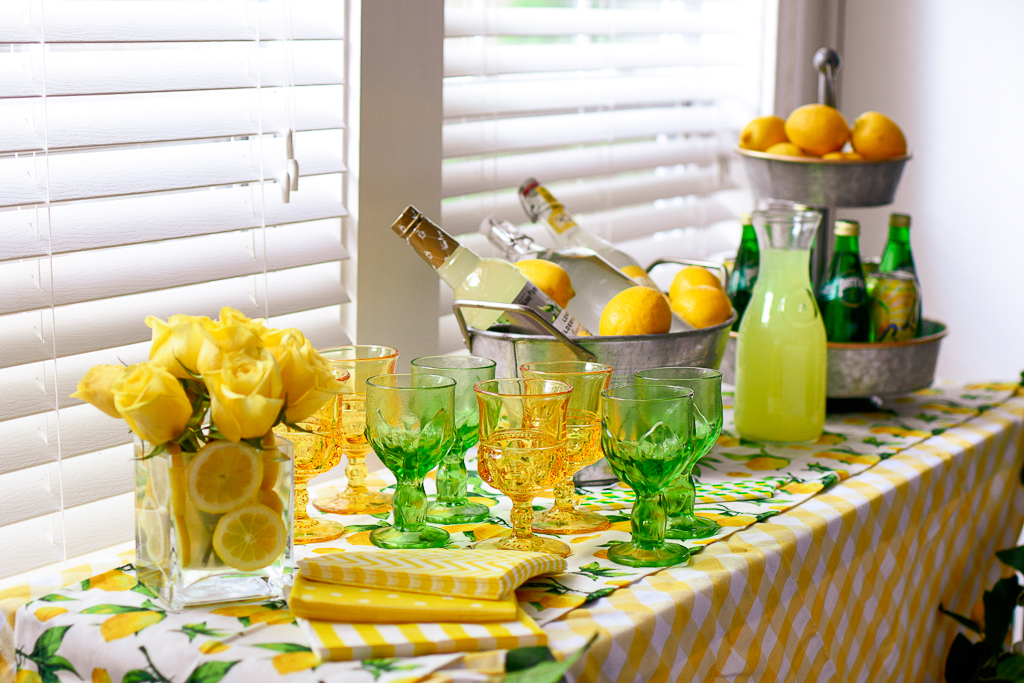 A great summer party themes is a DIY  lemonade stand ideas with is also a cute lemonade stand ideas. It include the best limoncello recipe, lemonade cocktail recipes and lemonade party ideas, a DIY burlap lemonade banner, galvanized pails, white and yellow check tablecloth, lemon table runner, galvanized tiered metal tray with lemons, vintage green glassware, vintage yellow glassware, and lemon garland.