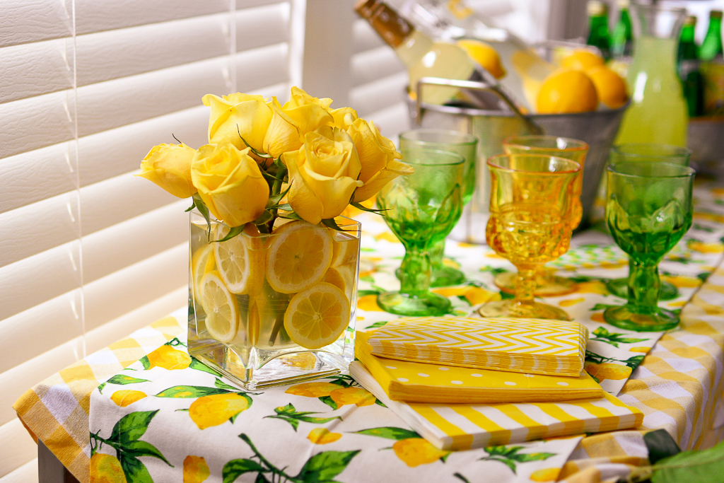 A great summer party themes is a DIY  lemonade stand ideas with is also a cute lemonade stand ideas. It include the best limoncello recipe, lemonade cocktail recipes and lemonade party ideas, a DIY burlap lemonade banner, galvanized pails, white and yellow check tablecloth, lemon table runner, galvanized tiered metal tray with lemons, vintage green glassware, vintage yellow glassware, and lemon garland, flower arrangement with yellow roses and cut lemons in a clear, square glass vase.